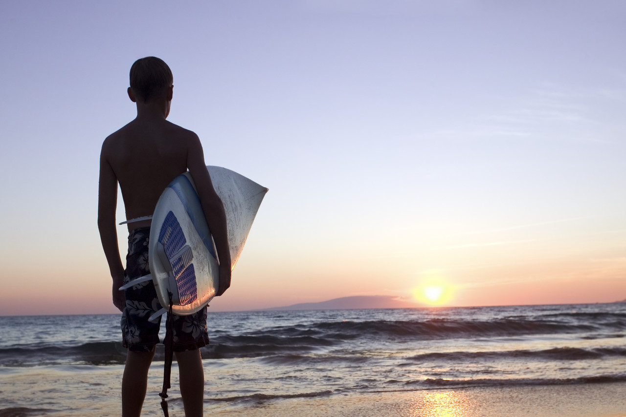 Surfer Holding Surfboard at Sunset